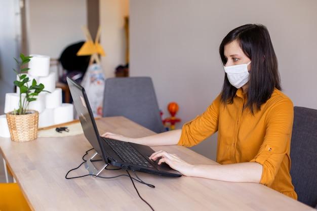 Koncepcja bezpiecznego pobytu w domu. ochrona przed koronawirusem zatrzymuje pandemię. młoda kobieta pracuje podczas choroby na laptopie w masce ochronnej. covid-19 freelancer internetowy programista technologii internetowych