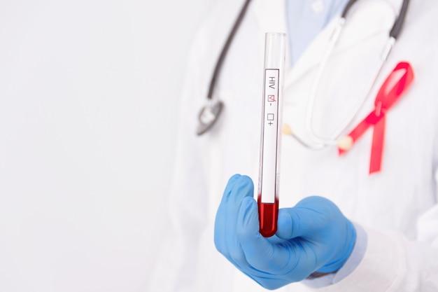 Koncepcja bezpiecznego seksu / opieki zdrowotnej. lekarz nosi biały płaszcz z przypiętą czerwoną wstążką jako symbol pomocy hiv i stetoskop trzyma ujemny marker nowotworowy