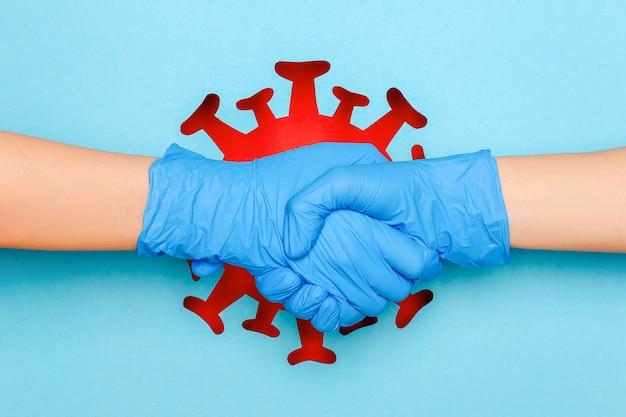 Koncepcja bezpiecznego uścisku dłoni podczas koronawirusa, epidemii, choroby zakaźnej. gest dłoni trzęsących się w lateksowych rękawiczkach przeciwko streszczenie czerwonego wirusa, bakterii, mikrobów na niebieskim tle.