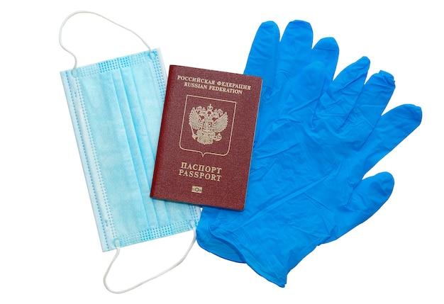 Koncepcja bezpiecznej podróży dookoła świata, łagodzenie kwarantanny po globalnej pandemii covid-19 - maska medyczna, rękawiczki medyczne i paszport zagraniczny, izolowane na białej przestrzeni