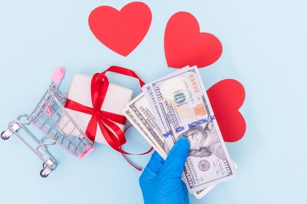 Koncepcja bezpiecznych zakupów. ręka w niebieskiej rękawicy medycznej trzyma dolary gotówkowe nad koszykiem