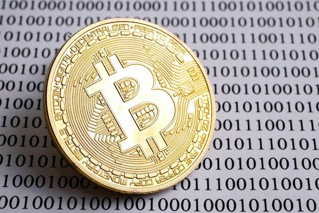 Koncepcja bitcoin jako lider kryptowaluty. złota moneta bitcoin przeciwko jednemu kodowi.