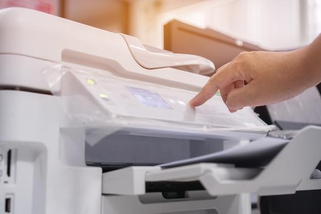 Koncepcja biura biznesowego ręka biznesmen naciśnij przycisk na panelu drukarki dla procesu dokumentacji na laserze
