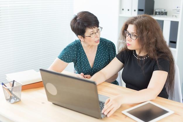 Koncepcja biura, ludzi biznesu i grafika - kobiety siedzą i omawiają pomysły w biurze z laptopem, patrząc na ekran, słuchając opinii.