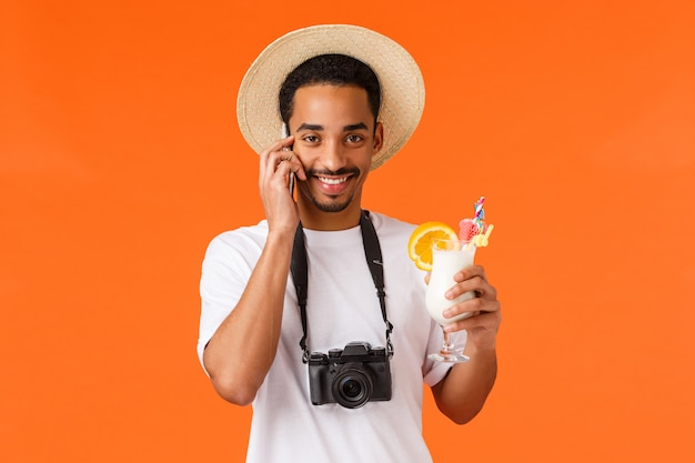 Koncepcja biura podróży, podróży i podróży. przystojny wesoły charyzmatyczny afroamerykański facet w kapeluszu, aparacie i białej koszulce, pijący koktajl, rozmawiający telefon, dzwoniący z zagranicy, pomarańczowy