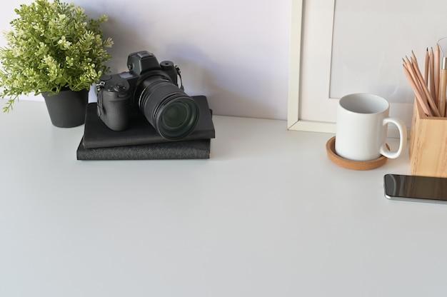 Koncepcja biurko fotografa. projektanci stół, kamera, kawa i ramka na zdjęcia kopiowanie miejsca.