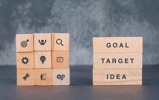 Koncepcja biznesowa cel z drewnianymi klockami z ikonami na to widok z boku.