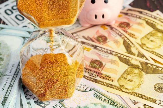 Koncepcja biznesowa czasu i pieniędzy. klepsydra i pieniądze