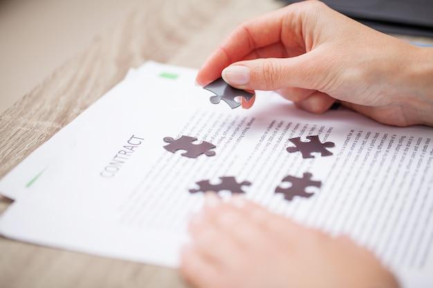 Koncepcja biznesowa, dłonie kobiety tworzą układankę symbolizującą sukces firmy