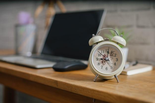 Koncepcja biznesowa harmonogram z budzikiem i laptopem na drewnianym stole.