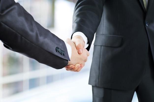 Koncepcja biznesowa i biurowa - biznesmen, ściskając ręce każdy inny