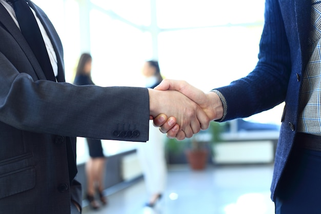 Koncepcja biznesowa i biurowa - dwóch biznesmenów ściskających sobie ręce w biurze