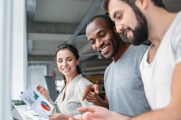 Koncepcja biznesowa i biurowa uśmiechnięty zespół omawiający osiągnięcia patrząc na wykresy