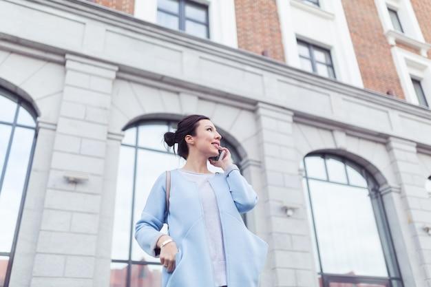 Koncepcja biznesowa i niezależny. młoda kobieta pracująca z telefonem komórkowym na ulicy z biurowcami w tle
