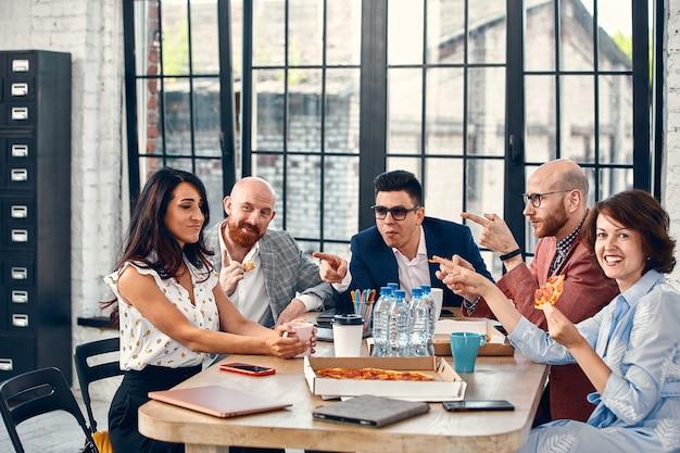 Koncepcja biznesowa, jedzenie, obiad i ludzie - szczęśliwy międzynarodowy zespół biznesowy jedzenie pizzy w biurze. outsider w zespole biurowym.