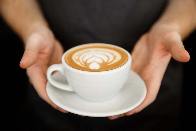 Koncepcja biznesowa kawy - przycinane zamknąć żeński obsługujących kawę z latte sztuki stojąc w kawiarni. skupić się na ręce kobiet, wprowadzanie filiżankę kawy.