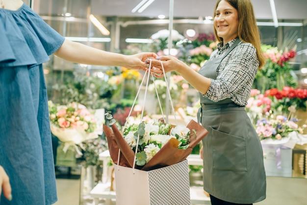 Koncepcja biznesowa kwiaciarni, kwiaciarnia w fartuch i klientka w butiku kwiatowym.