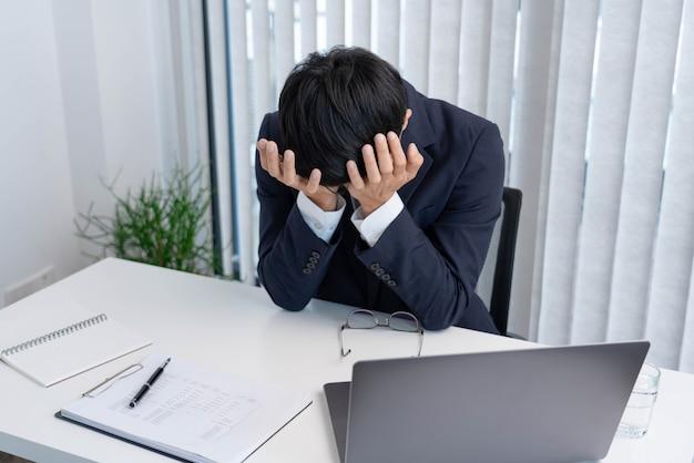 Koncepcja biznesowa mężczyzna wykonawczy stojący przed wielką awarią, zdesperowany, samotny w swoim biurze pracy.