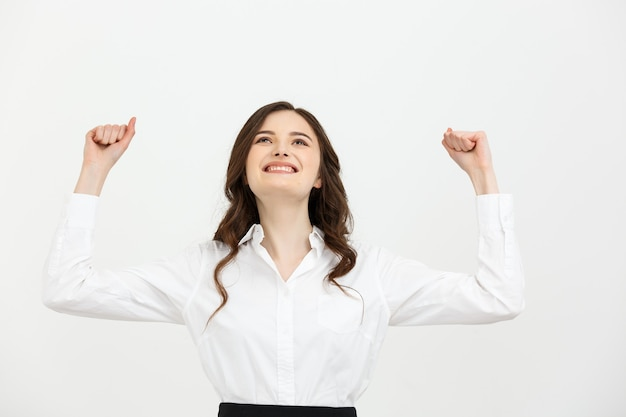 Koncepcja biznesowa młoda szczęśliwa bizneswoman z rękami w powietrzu świętuje sukces