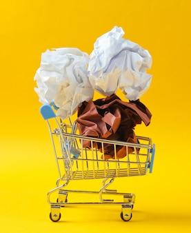 Koncepcja biznesowa pakietu office. zmięte papierowe piłki w mini wózek na zakupy na żółtym stole.