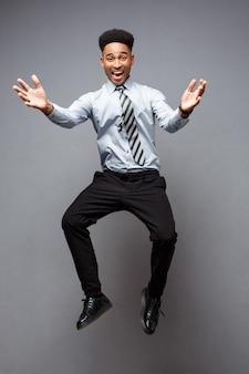 Koncepcja biznesowa - pełna długość portret udanego biznesmena afroamerykanów szczęśliwy skoki w biurze.