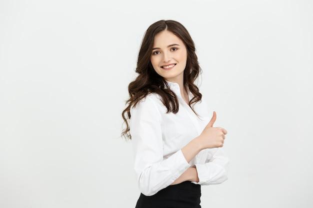 Koncepcja biznesowa pewnie młoda kobieta wesoły pokazując kciuk na białym tle