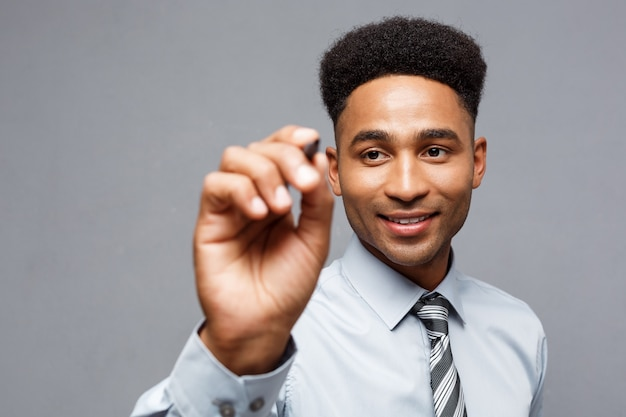 Koncepcja biznesowa - pewny siebie african american businessmanager przygotowany do pisania na wirtualnej tablicy lub szkle w biurze.
