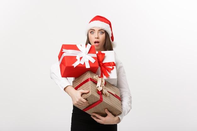 Koncepcja biznesowa piękna młoda biznesowa kobieta kaukaski z santa hat trzyma wiele pudełek z prezentami z zaskakującym wyrazem twarzy