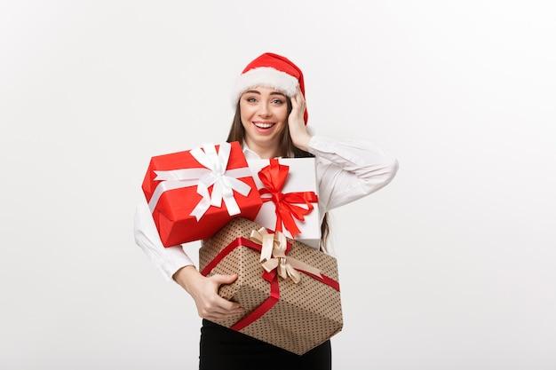 Koncepcja biznesowa piękna młoda kobieta kaukaska biznesu z santa hat trzyma dużo pudełek na prezenty świąteczne z miejscem na kopię z boku