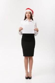 Koncepcja biznesowa - piękna młoda kobieta pewnie biznesu z santa hat trzymając biały czysty papier świętują na boże narodzenie.