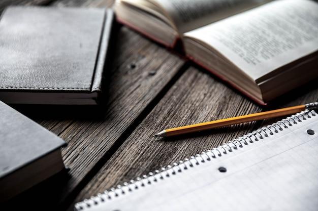 Koncepcja biznesowa, pomysły, książki i zeszyt na drewnianym stole z ołówkami