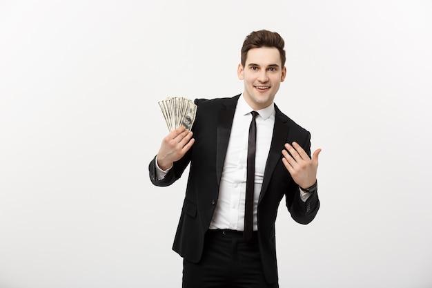Koncepcja biznesowa: portret przystojny biznesmen garnitur gospodarstwa wentylator dolar gotówki na białym tle nad białym szarym tle.