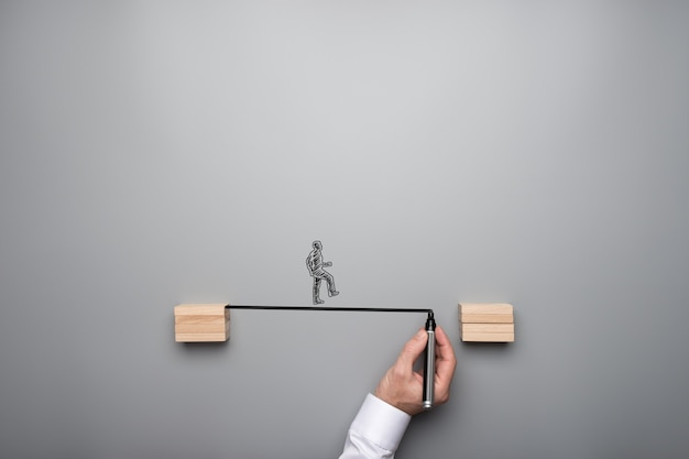 Koncepcja biznesowa pracy zespołowej i strategii - męskiej ręki rysowanie mostu między dwoma drewnianymi kostkami
