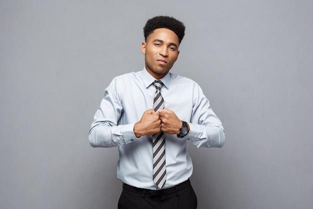 Koncepcja biznesowa - przekonany, wesoły młody afroamerykanin w boksie poseture na szarej ścianie.