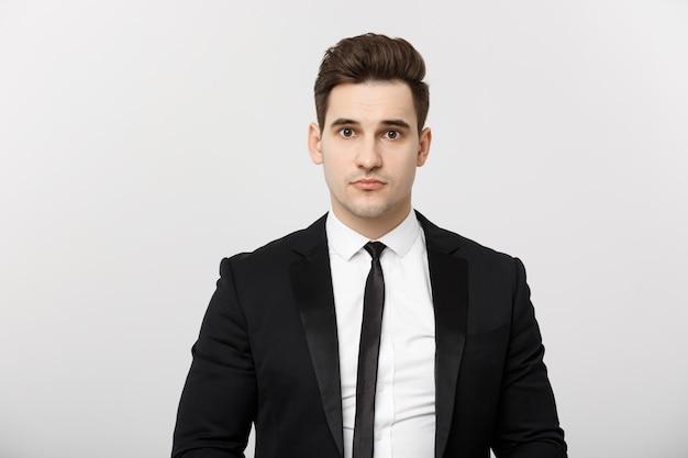 Koncepcja biznesowa przystojny mężczyzna szczęśliwy uśmiech młody przystojny facet w eleganckim garniturze pozuje na szarym tle...