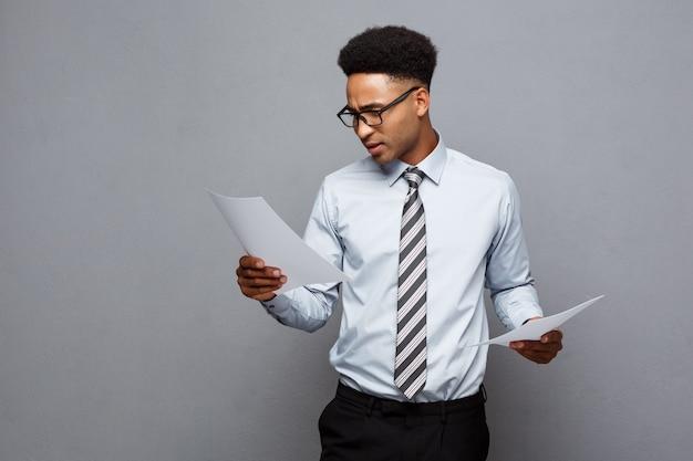Koncepcja biznesowa - przystojny młody biznesmen afroamerykanów zawodowych skoncentrowane czytanie na papierze dokumentu.