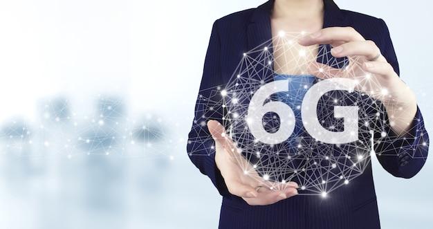 Koncepcja biznesowa sieci 6g internet mobile wireless. dwie ręce trzymając wirtualną holograficzną ikonę 6g z jasnym niewyraźnym tłem. streszczenie światowe połączenie sieciowe, internet i globalne połączenie