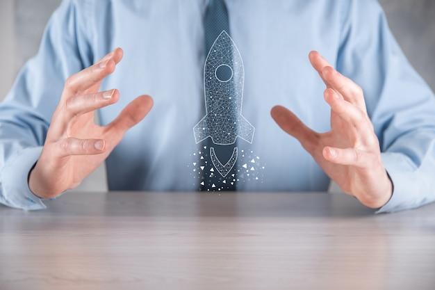 Koncepcja biznesowa start-upu, biznesmen posiadający ikonę przezroczystej rakiety wystrzeliwuje i szybuje wylatując z ekranu z połączeniem sieciowym na ciemnej ścianie.