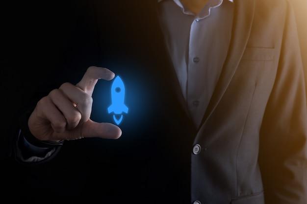 Koncepcja biznesowa start-upu, biznesmen trzymający tablet i rakietę ikona uruchamia się i szybuje wylatując z ekranu z połączeniem sieciowym w ciemności.