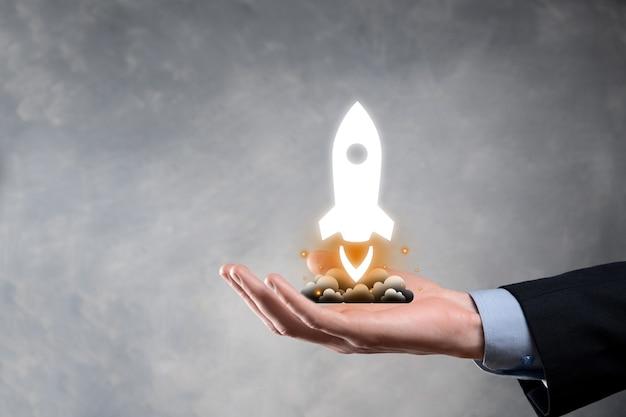 Koncepcja biznesowa start-upu, biznesmen trzymający tablet i rakietę z ikoną uruchamia się i szybuje wylatując z ekranu z połączeniem sieciowym na ciemnym tle