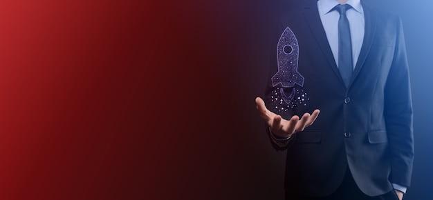 Koncepcja biznesowa start-upu, biznesmen trzymający tablet i rakietę z ikoną uruchamia się i szybuje wylatując z ekranu z połączeniem sieciowym na ciemnym tle.