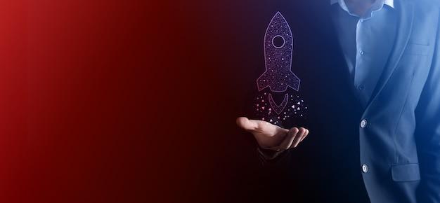 Koncepcja biznesowa startupu, trzymając tablet i ikonę rakiety, wystrzeliwuje szybowiec wylatujący z ekranu