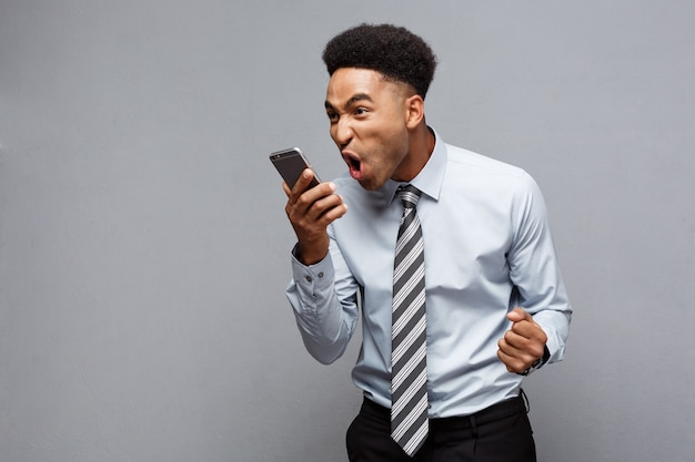 Koncepcja biznesowa - stresujący biznesmen african american krzyczy i krzyczy na telefon komórkowy.