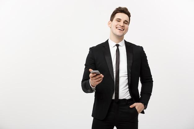 Koncepcja biznesowa: szczęśliwy młody biznesmen w eleganckim garniturze, piszący sms na szarym tle