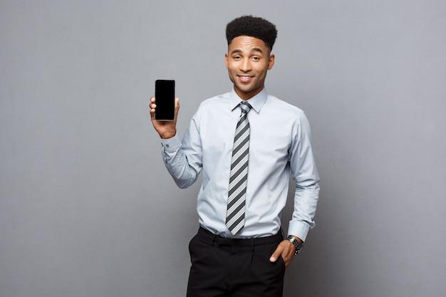 Koncepcja biznesowa - szczęśliwy przystojny biznesmen afroamerykanów zawodowych pokazując telefon komórkowy klientowi.