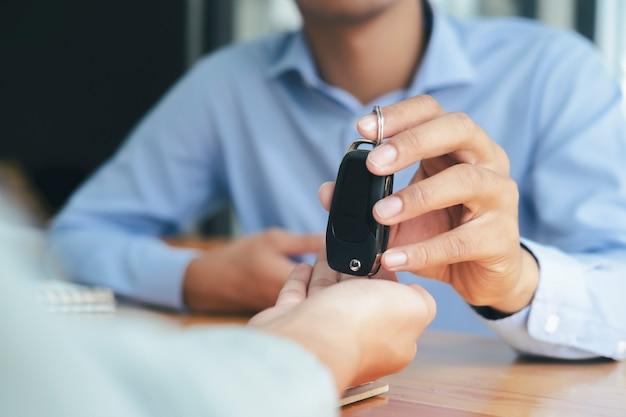 Koncepcja biznesowa, ubezpieczenie samochodu, sprzedaż i kupno samochodu, finansowanie samochodu, kluczyk do umowy sprzedaży pojazdu. nowi właściciele samochodów odbierają klucze od sprzedawców płci męskiej.