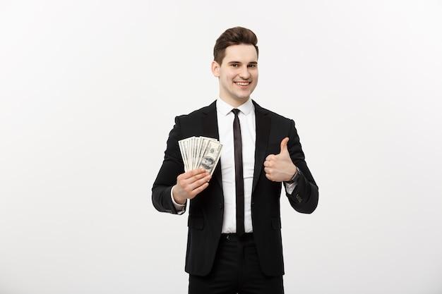 Koncepcja biznesowa - udany biznesmen posiadający banknoty dolarowe i pokazujący kciuk w górę na białym tle nad białym tłem.