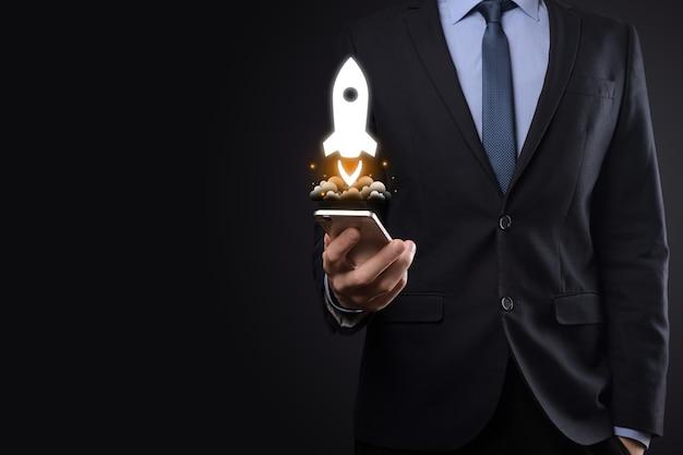 Koncepcja biznesowa uruchomienia, biznesmen trzymając tablet i rakieta ikona jest uruchamiany i szybuje wylatuje z ekranu z połączeniem sieciowym na ciemnym tle