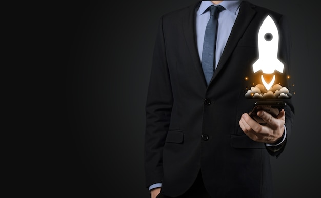 Koncepcja biznesowa uruchomienia, biznesmen trzymając tablet i rakieta ikona jest uruchamiany i szybuje wylatuje z ekranu z połączeniem sieciowym na ciemnym tle.