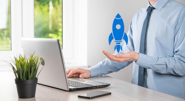 Koncepcja biznesowa uruchomienia, biznesmen trzymający tablet i ikonę rakiety uruchamia się i szybuje w powietrzu